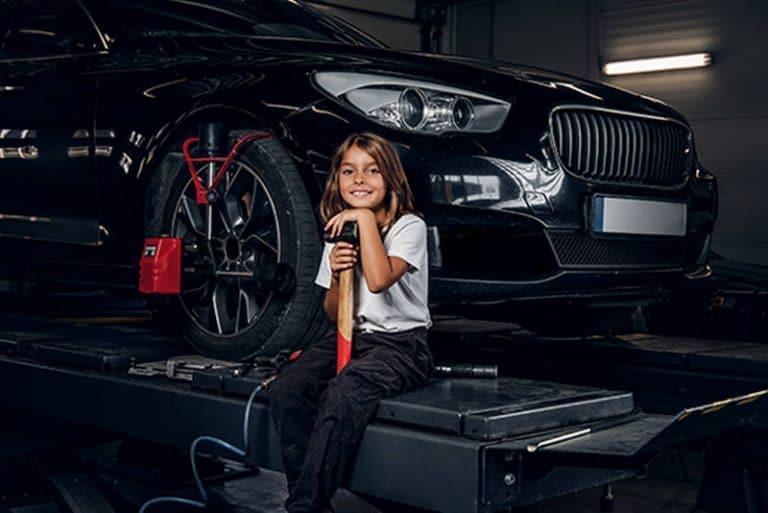 Kind auf der Hebebühne in der Werkstatt